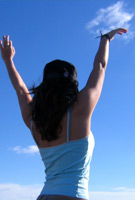 Young woman reaching up to sky